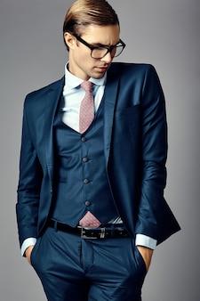Młody elegancki przystojny biznesmen samiec model w kostiumu i modnych szkłach pozuje w studiu