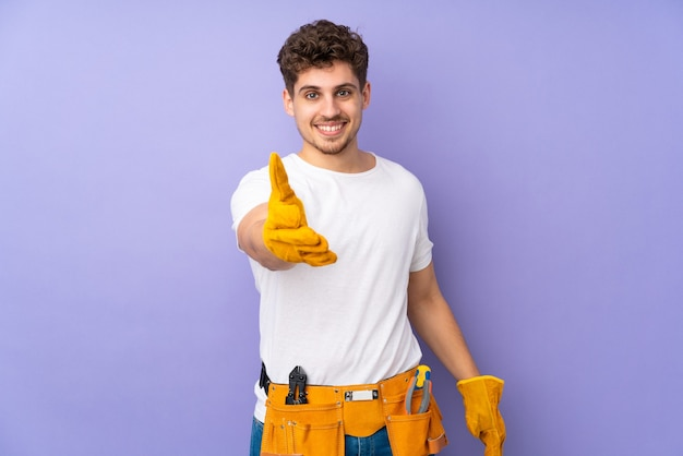 Młody elektryk mężczyzna na białym tle na fioletowy uścisk dłoni po dobrej transakcji