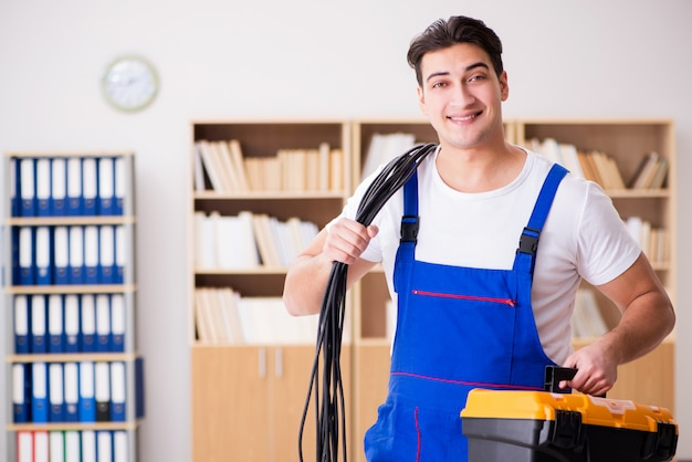 Młody elektryk z kablowym działaniem w biurze