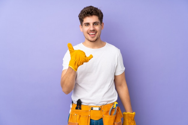 Młody elektryka mężczyzna na purpury ścianie robi telefonu gestowi