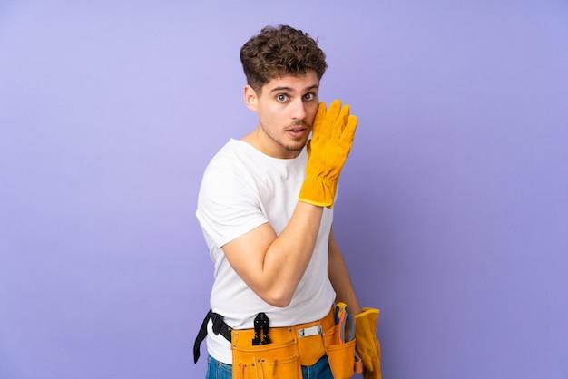 Młody elektryka mężczyzna na purpury ścianie szepcze coś