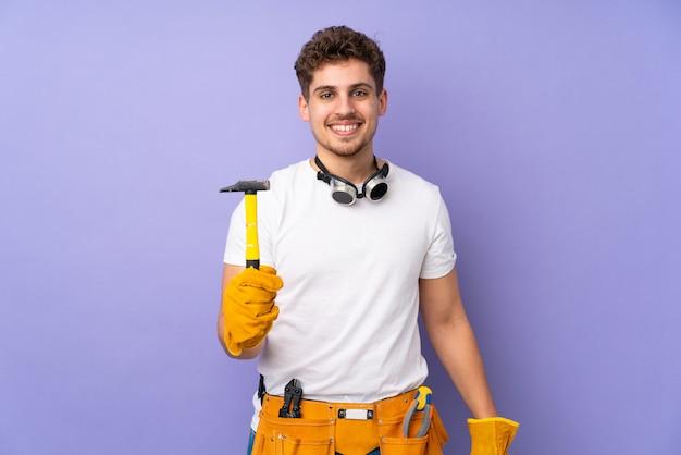 Młody elektryka mężczyzna na purpury ścianie