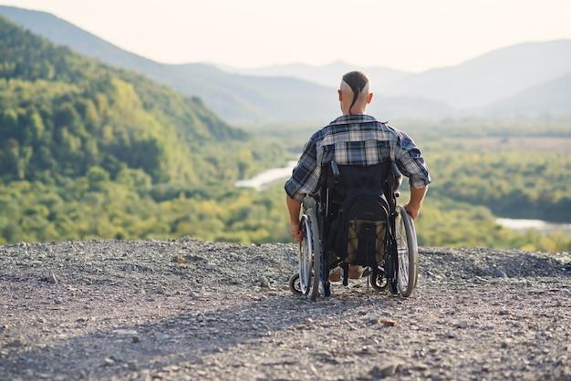 Młody emerytowany wojskowy na wózku inwalidzkim, ciesząc się świeżym powietrzem w słoneczny dzień na górze