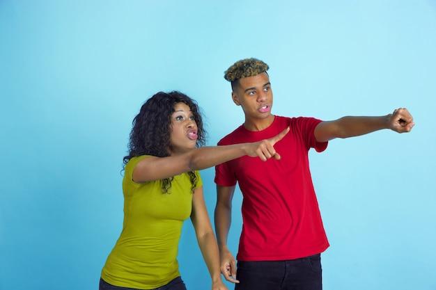 Młody emocjonalny afroamerykanin i kobieta całkowicie zszokowany patrzą z boku jak fani sportu na niebiesko