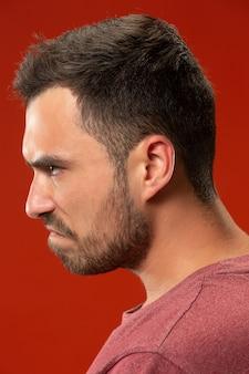 Młody emocjonalny gniewny mężczyzna krzyczy na czerwonej studio ścianie