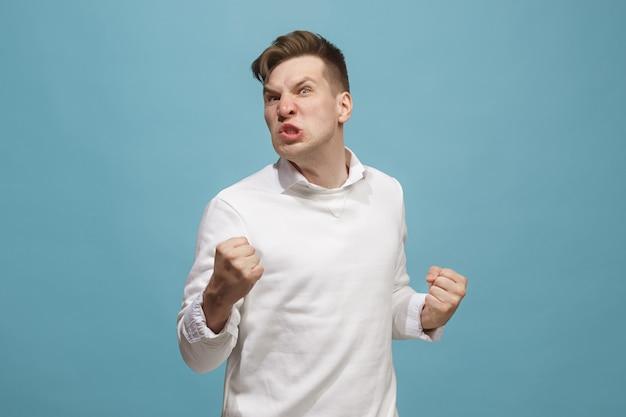 Młody emocjonalny gniewny mężczyzna krzyczy na pracownianym tle