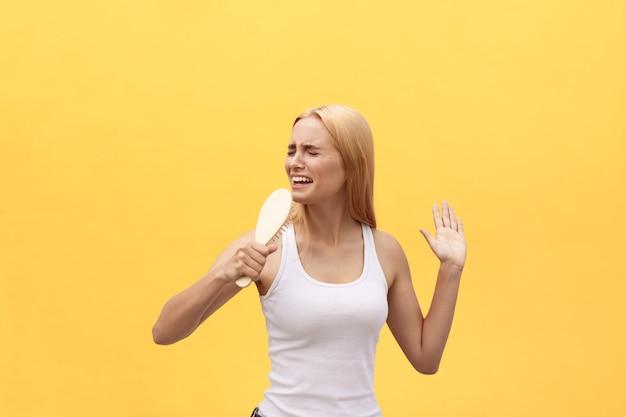 Młody emocjonalny kobieta śpiew z gręplą podczas gdy ubierający. pojedynczo na żółtym tle.