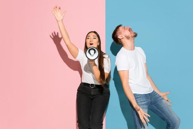 Młody emocjonalny mężczyzna i kobieta na różowej i niebieskiej ścianie