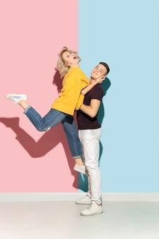 Młody emocjonalny mężczyzna i kobieta na różowym i niebieskim