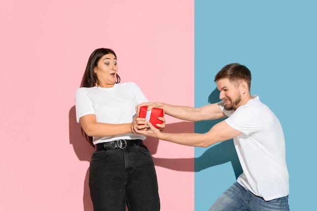 Młody emocjonalny mężczyzna i kobieta na ścianie różowy i niebieski