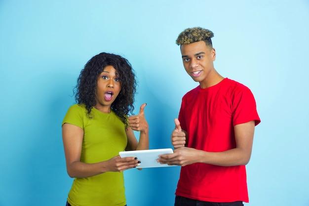 Młody emocjonalny mężczyzna i kobieta w kolorowe ubranie na niebiesko.