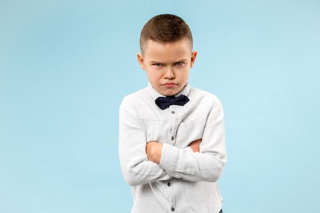 Młody emocjonalny zły nastolatek chłopiec na niebieskiej przestrzeni