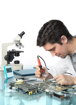 Młody energiczny męski technik lub inżynier naprawia sprzęt elektroniczny
