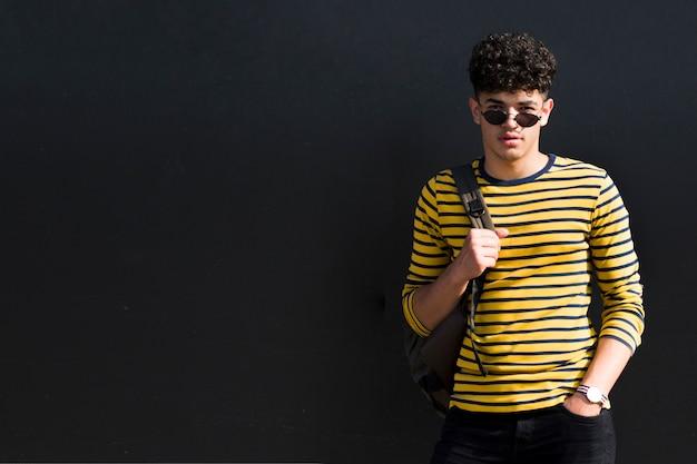 Młody etniczny kędzierzawy mężczyzna w okularach przeciwsłonecznych z plecakiem przeciw czarnemu tłu