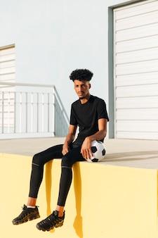 Młody etniczny mężczyzna siedzi z piłki nożnej