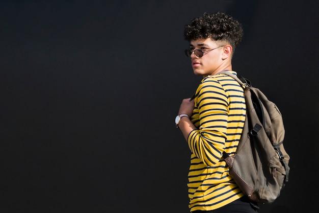 Młody etniczny mężczyzna w okularach przeciwsłonecznych z plecakiem przeciw czarnemu tłu