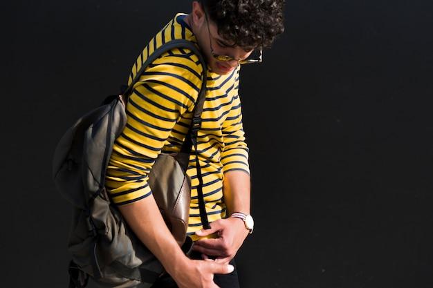 Młody etniczny samiec z kędzierzawym włosy i plecakiem w pasiastej koszula patrzeje z powrotem