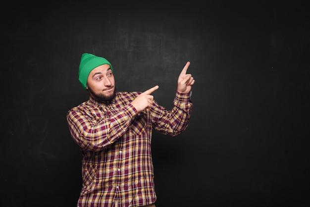 Młody europejczyk z brodą w zielonej czapce wygląda na zaskoczonego i zdziwionego. pokazuje palce w górę i po prawej stronie. czarne tło, puste miejsce na tekst lub reklamę