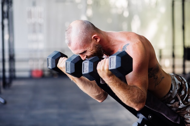Młody europejski mężczyzna z wytatuowanym mięśniami i wytatuowanymi mięśniami robi ciężkie ćwiczenia