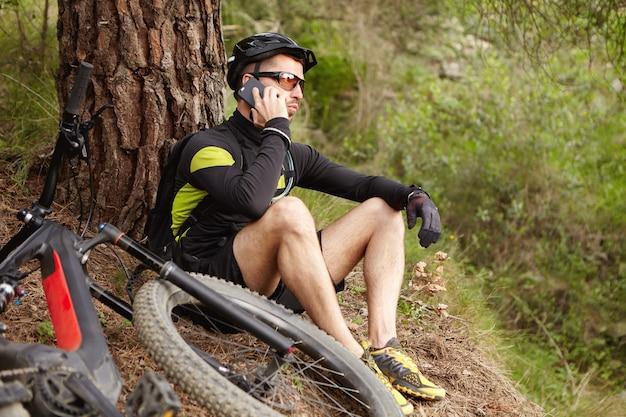 Młody europejski rowerzysta w odzieży sportowej odpoczywa w lesie rozmawia przez telefon komórkowy