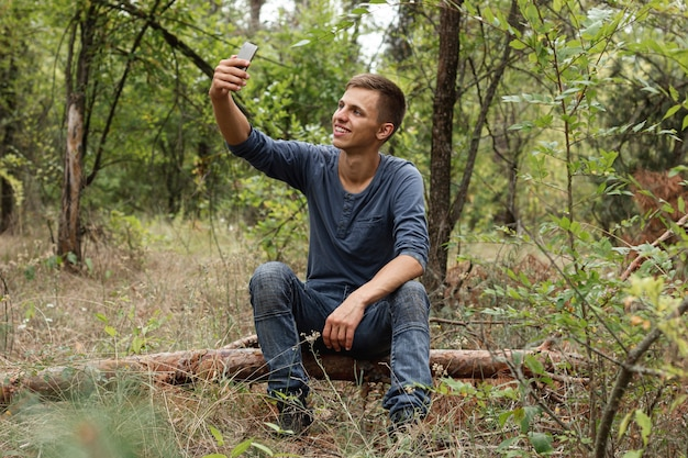 Młody facet bierze selfie w lesie