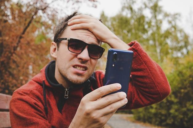 Młody facet czyta wiadomości lub sms-y na telefonie komórkowym i trzyma rękę za głowę. rozczarowanie wiadomością w telefonie. problemy w komunikacji online. rozczarowujące, sfrustrowane.