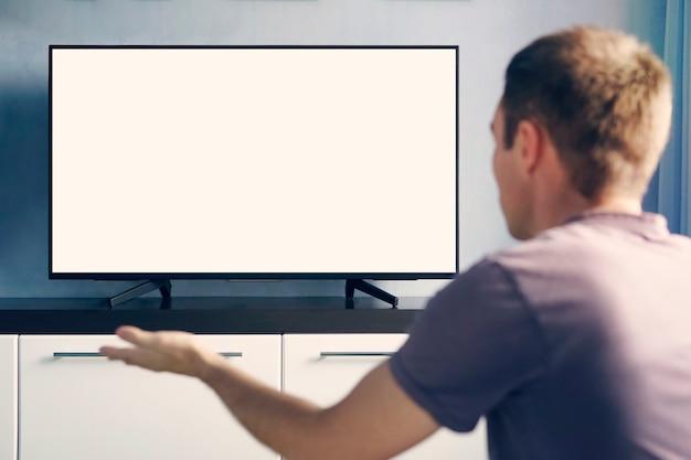 Młody facet emocjonalnie ogląda telewizję i macha rękami z niezadowoleniem. pusty biały ekran do projektowania.