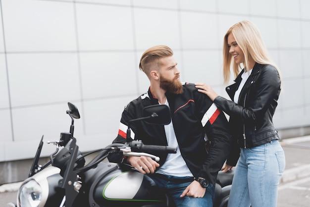 Młody facet i dziewczyna siedzi na nowoczesnym motocyklu elektrycznym