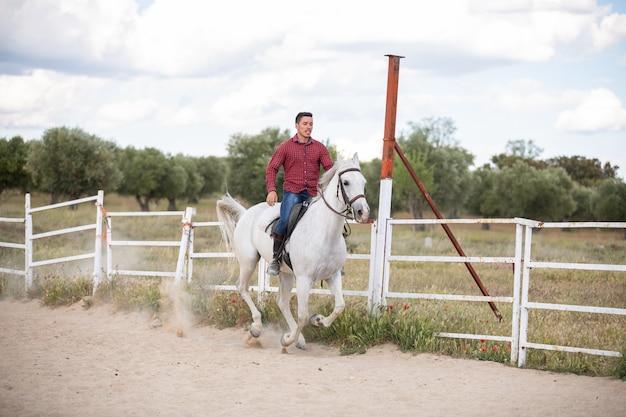 Młody facet jedzie białego konia na piaskowatej ziemi w przypadkowym stroju
