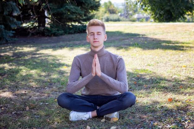 Młody facet medytuje w parku. umieść pod napisem.