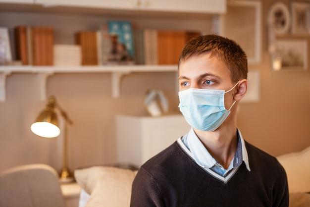 Młody facet o europejskim wyglądzie, siedzący wygodnie na kanapie w koncepcji maski medycznej, czekając...