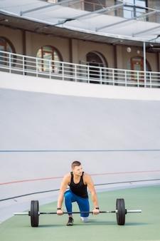 Młody facet podnosi poprzeczkę na stadionie, trening na świeżym powietrzu