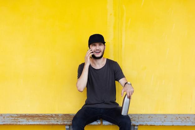 Młody facet siedzi na krześle stacji, rozmawia na smartfonie, trzymając na nodze stalową butelkę termiczną do wody