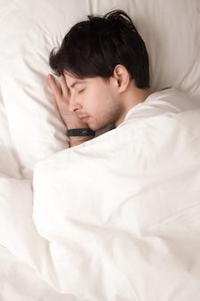 Młody facet śpi w łóżku na sobie elegancki zegarek, tracker snu