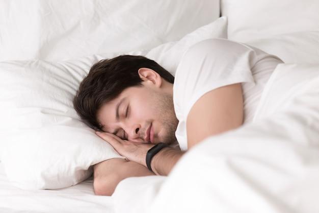 Młody facet śpi w łóżku na sobie smartwatch lub tracker snu