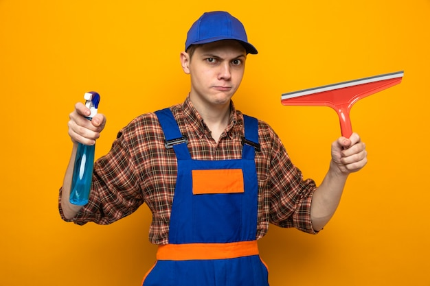 Młody facet sprzątający ubrany w mundur i czapkę, trzymający środek czyszczący z głowicą mopa odizolowaną na pomarańczowej ścianie