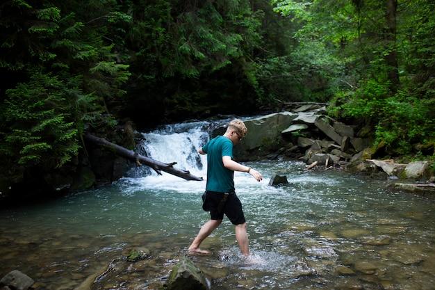 Młody facet stoi nad rzeką na tle wodospadu