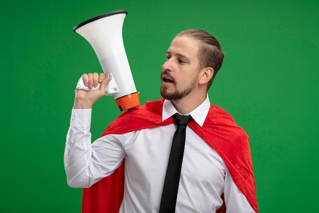 Młody facet superbohatera i umieszczenie głośnika na ramieniu na białym tle na zielono