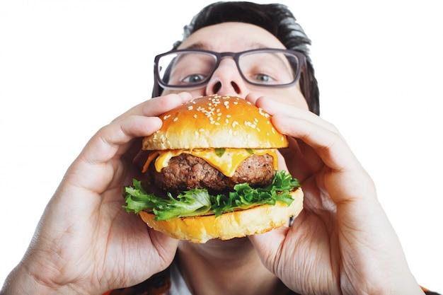 Młody facet trzyma świeżego burger.