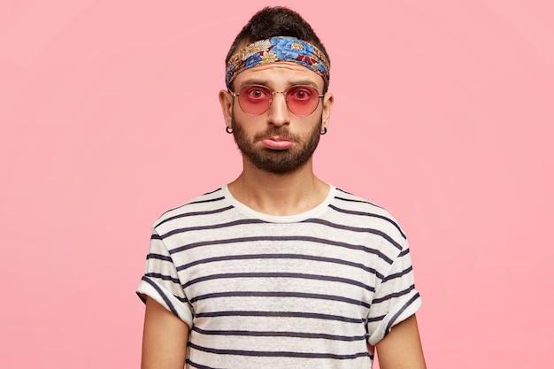 Młody facet ubrany w chustkę i stylowe okulary przeciwsłoneczne