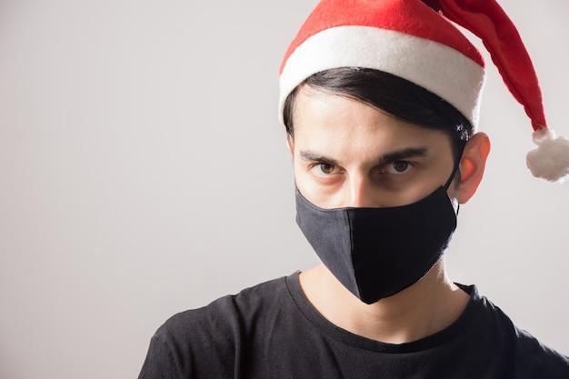 Młody facet ubrany w świąteczny kapelusz i maskę na twarz