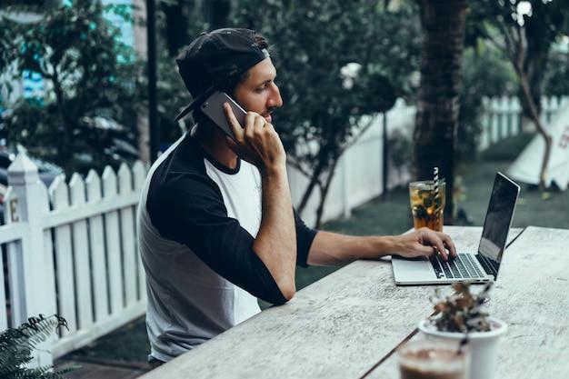 Młody facet używa smartfona w kawiarni, surfuje po internecie, ogląda filmy, pije