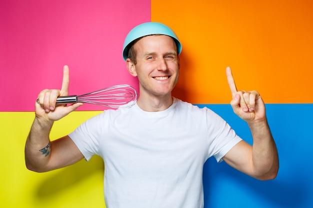 Młody facet w białej koszulce, kolorowe tło, naczynia kuchenne, kucharz, emocje zdjęcie