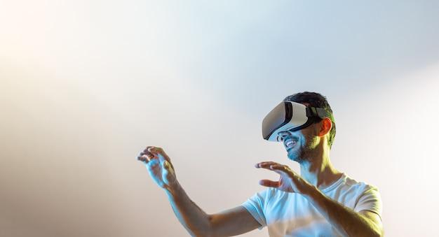 Młody facet w białej koszulce, uśmiechnięty w okularach wirtualnej rzeczywistości i uniesionymi rękami, patrząc w lewo oświetlony żółtymi i niebieskimi światłami z różowawym tłem i przestrzenią do kopiowania