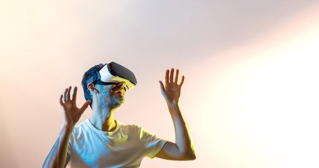 Młody facet w białej koszulce, uśmiechnięty w okularach wirtualnej rzeczywistości i uniesionymi rękami, patrząc w prawo, oświetlony żółtymi i niebieskimi światłami z różowawym tłem i przestrzenią do kopiowania