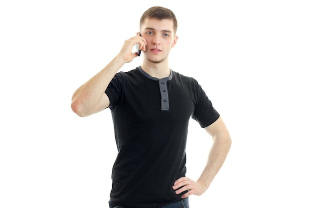 Młody facet w czarnej koszulce dzwoni na telefon komórkowy na białym tle na białej ścianie