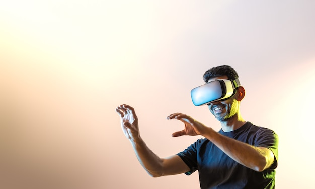 Młody facet w czarnej koszulce z okularami wirtualnej rzeczywistości i uniesionymi rękami patrząc w lewo oświetlony żółtymi i niebieskimi światłami z różowawym tłem i przestrzenią do kopiowania