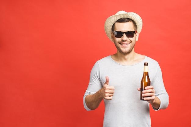 Młody facet w kapeluszu i okularach przeciwsłonecznych na białym tle na czerwonym tle trzyma butelkę piwa