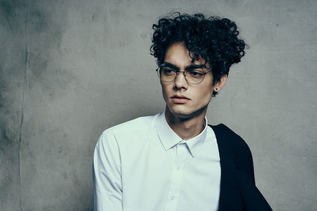 Młody facet w okularach kręcone włosy kurtka portret zbliżenie