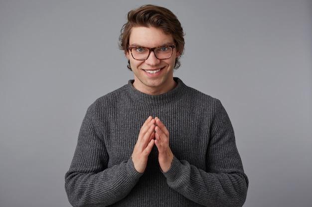 Młody facet w okularach nosi szary sweter, stoi na szarym tle, powinien być złożony w dłoni i podstępnie patrzeć w obiektyw.